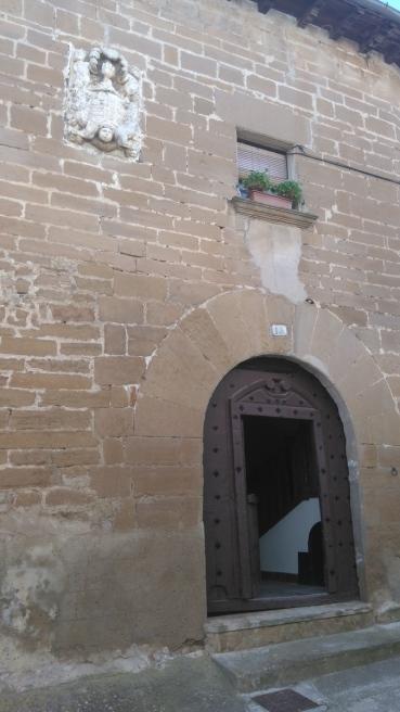 Beaucoup de belles portes et les armes de Navarre au mur de la maison.